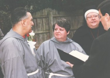 Connie and Charlie saying their vows, wearing Fransican monk outfits that she had sewn herself.